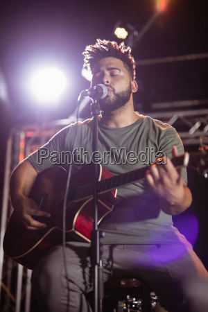 male musician with eyes closed singing