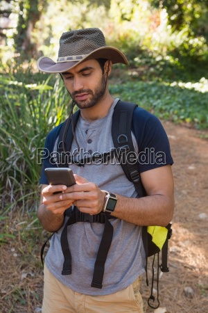 man with backpack using mobile phone