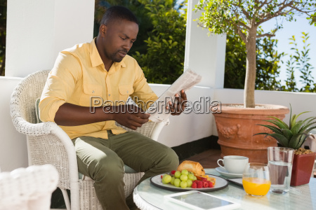 young man reading newspaper by breakfast