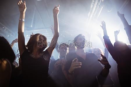 happy people dancing at nightclub