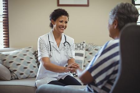 female doctor comforting senior woman in