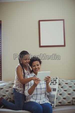 mother and daughter using digital tablet