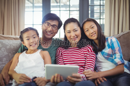smiling family using digital tablet together