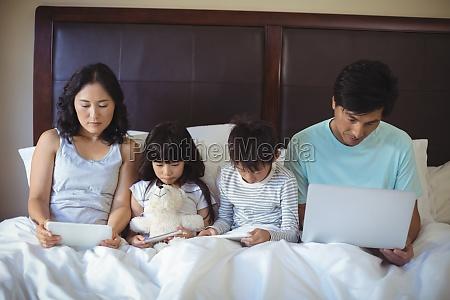 family using digital tablet mobile phone