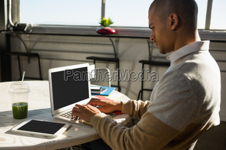 concentrated man using laptop at office