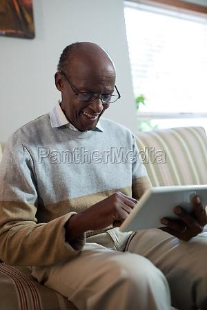 happy senior man using tablet