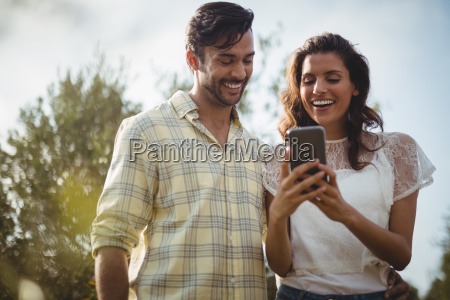 cheerful young couple using mobile phone