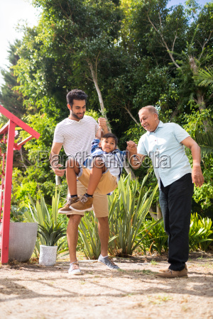 playful father and grandfather with boy