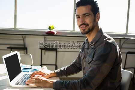 portrait, of, man, using, laptop, at - 23092289