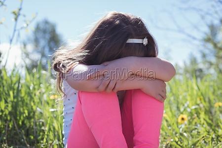 sad girl sitting in parkland