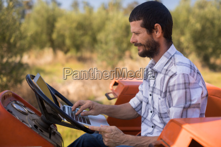 man using laptop in tractor