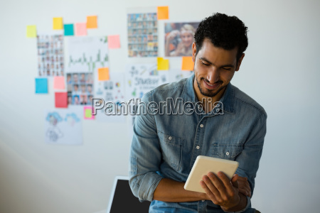 man using tablet against adhesive notes