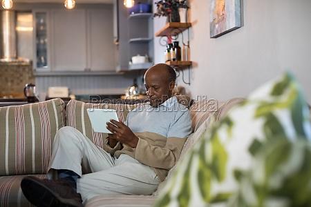 senior man using tablet computer in