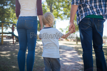 parents and boy holding hands while