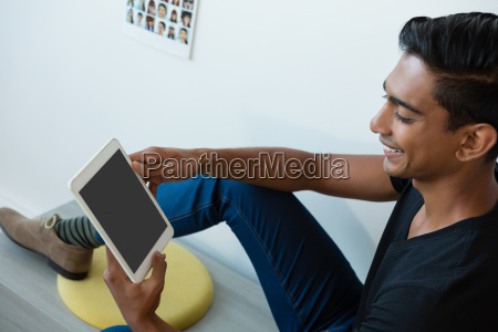 smiling man using tablet at office