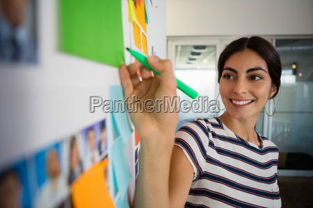 smiling woman writing on sticky note