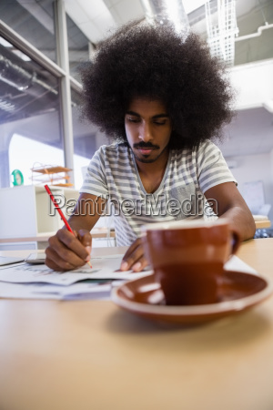 man writing on document at office