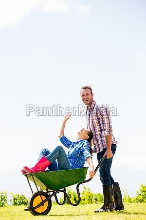 man pushing woman sitting in wheelbarrow