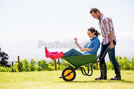 young man pushing woman sitting in