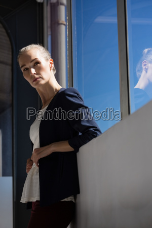 thoughtful businesswoman looking away while standing