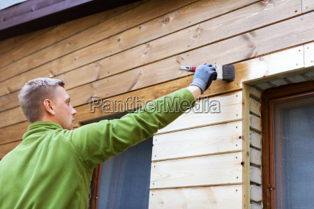 painter with paintbrush painting house wooden