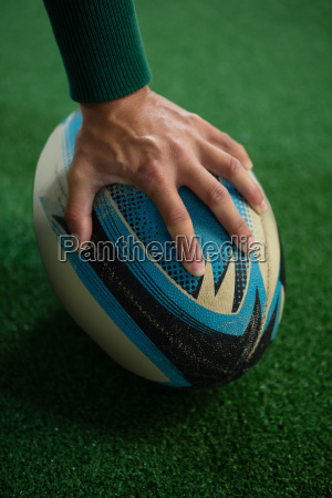cropped image of hand holding rugby