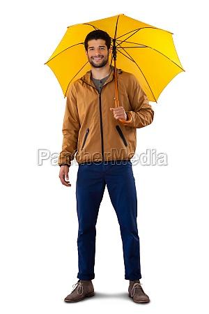 smiling man standing under umbrella against
