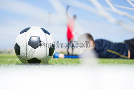 goalkeeper lying on field while playing