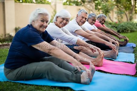 happy senior people doing stretching exercises