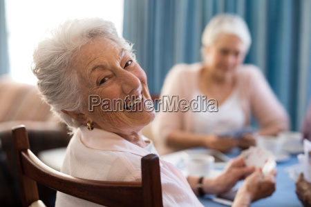 smiling senior woman playing cards with