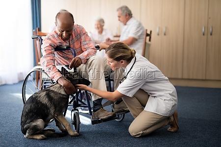 female doctor kneeling by disabled senior