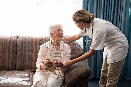 cheerful senior woman holding knitting wool