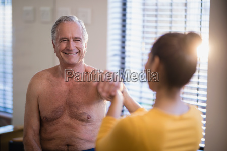 smiling shirtless senior male patient looking