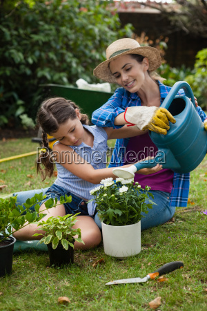 daughter assisting mother in watering potted