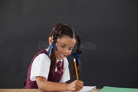 schoolgirl doing her homework against chalkboard