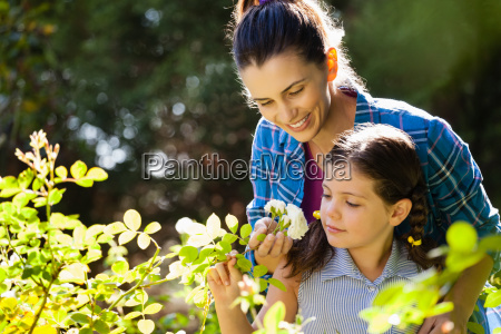 smiling woman with daughter smelling white
