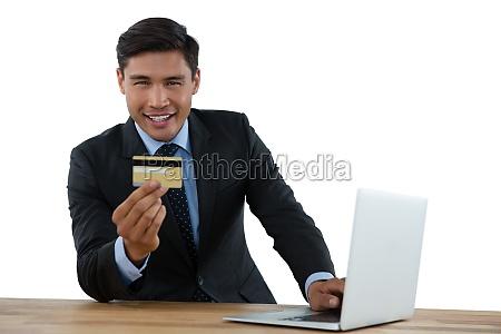 portrait of businessman holding credit card