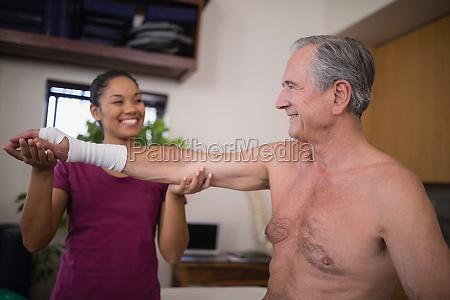 smiling female therapist looking at senior