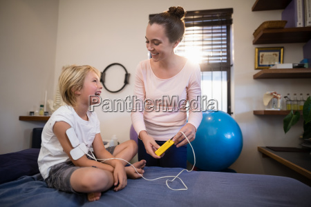 cheerful female therapist and boy looking
