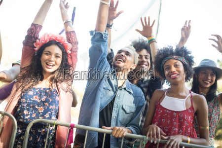 happy friends with arms raised enjoying