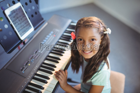 portrait of elementary girl practicing piano