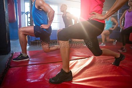 back lit athletes practicing lunge exercise