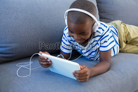 smiling boy using digital tablet while