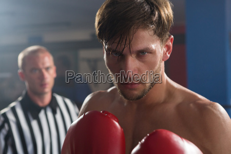 referee looking at young male boxer
