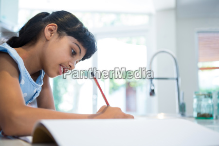 side view of girl writing in