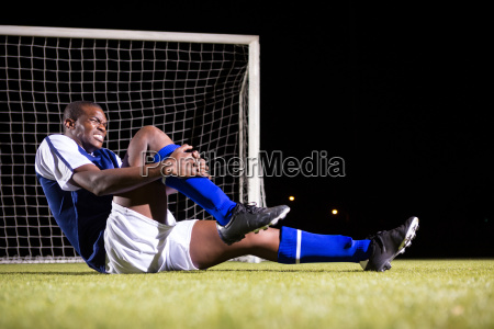 young male soccer player suffering from