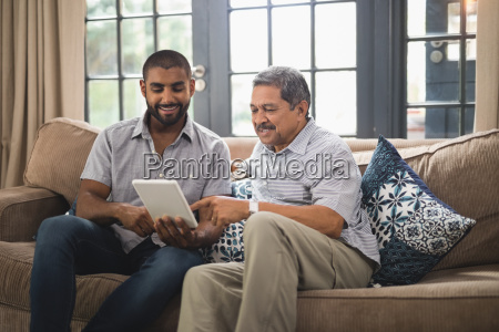 smiling man with father using digital