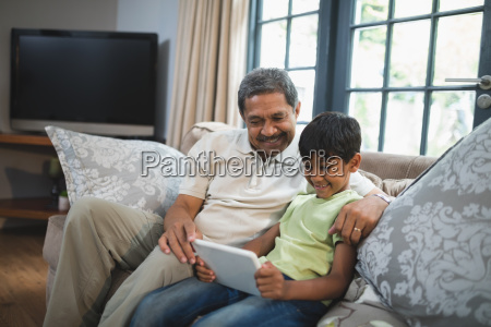smiling boy with grandfather using digital
