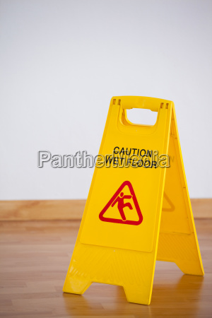 wet floor caution sign on wooden