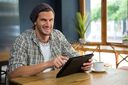 portrait of smiling man using tablet